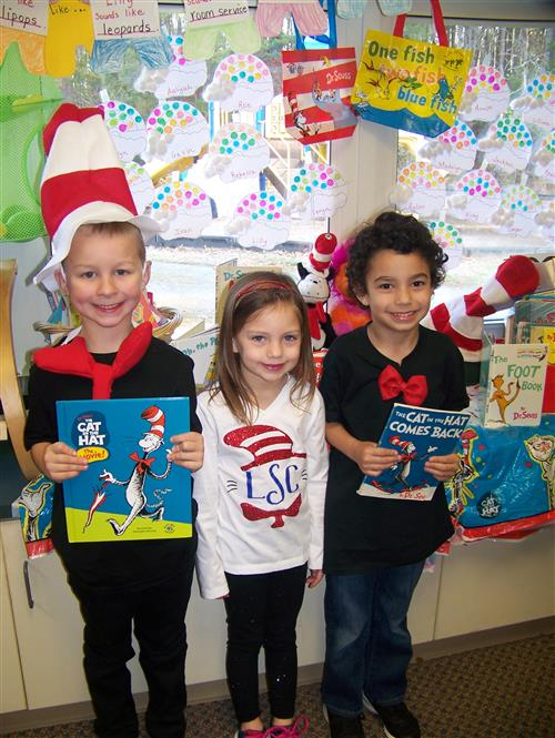 Mr. Brown's girls' are holding their favorite Dr. Seuss book, Mr. Brown Can Moo, Can You?