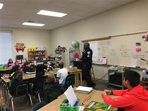 Policeman talking to 5th grade on Career Day.